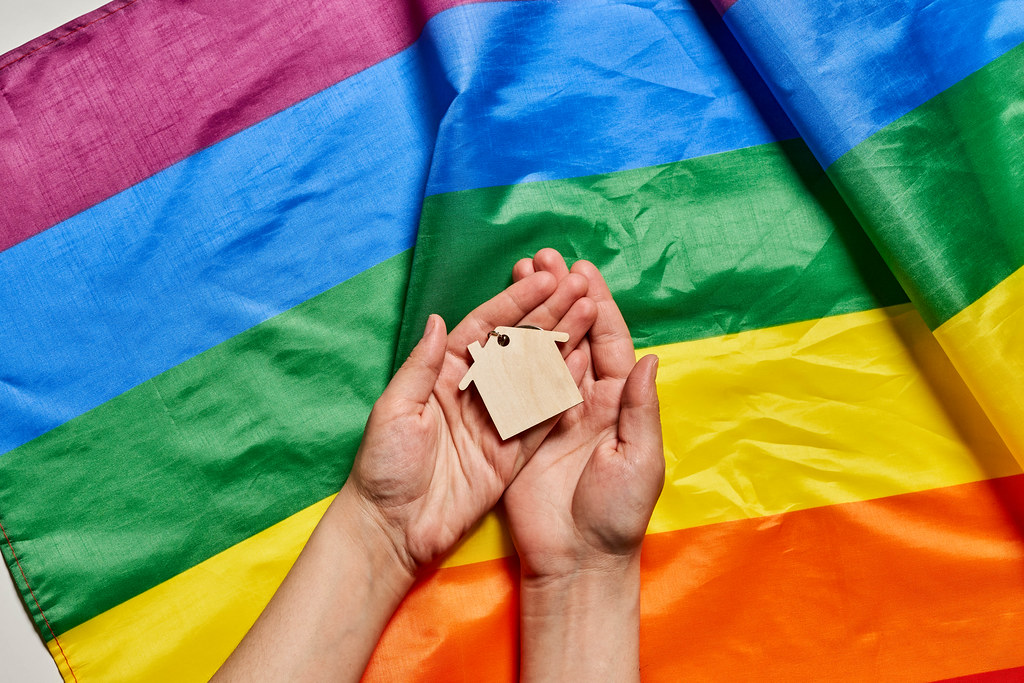 Female hand holding small wooden house over rainbow gay pride LGBT flag