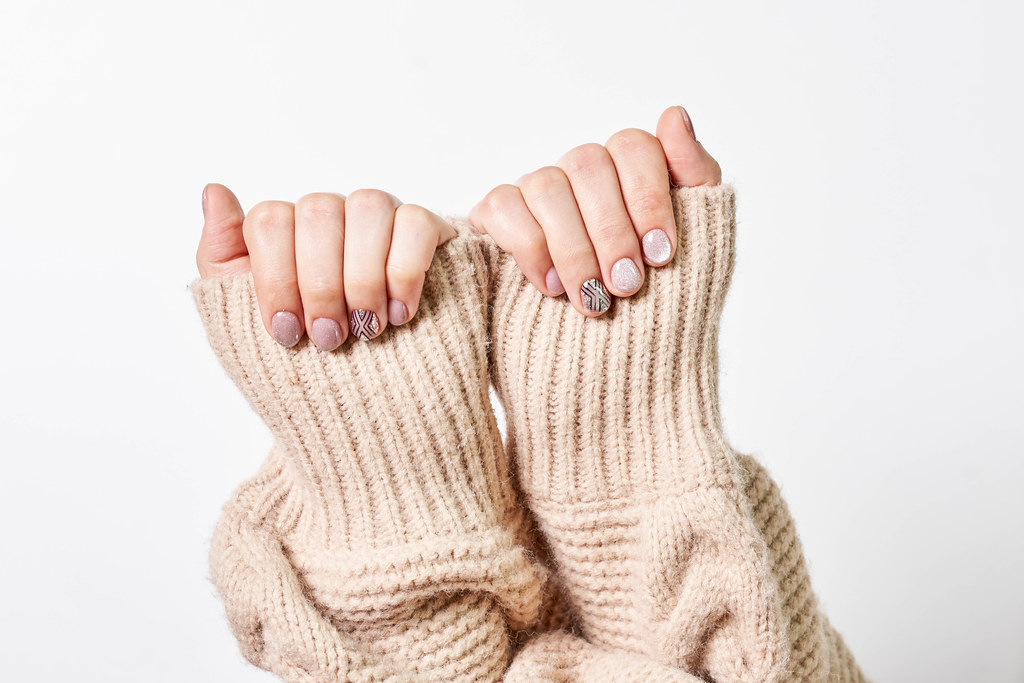 Female hand in a knitted sweater with trendy beautiful manicure