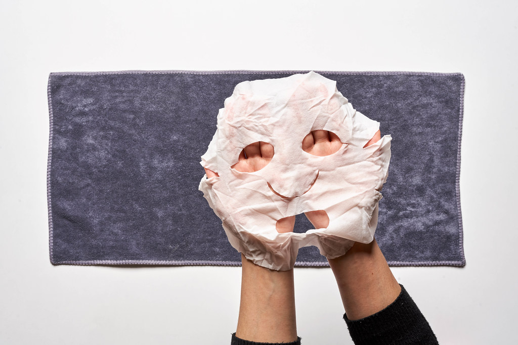Female hands hold a fabric mask for facial skin