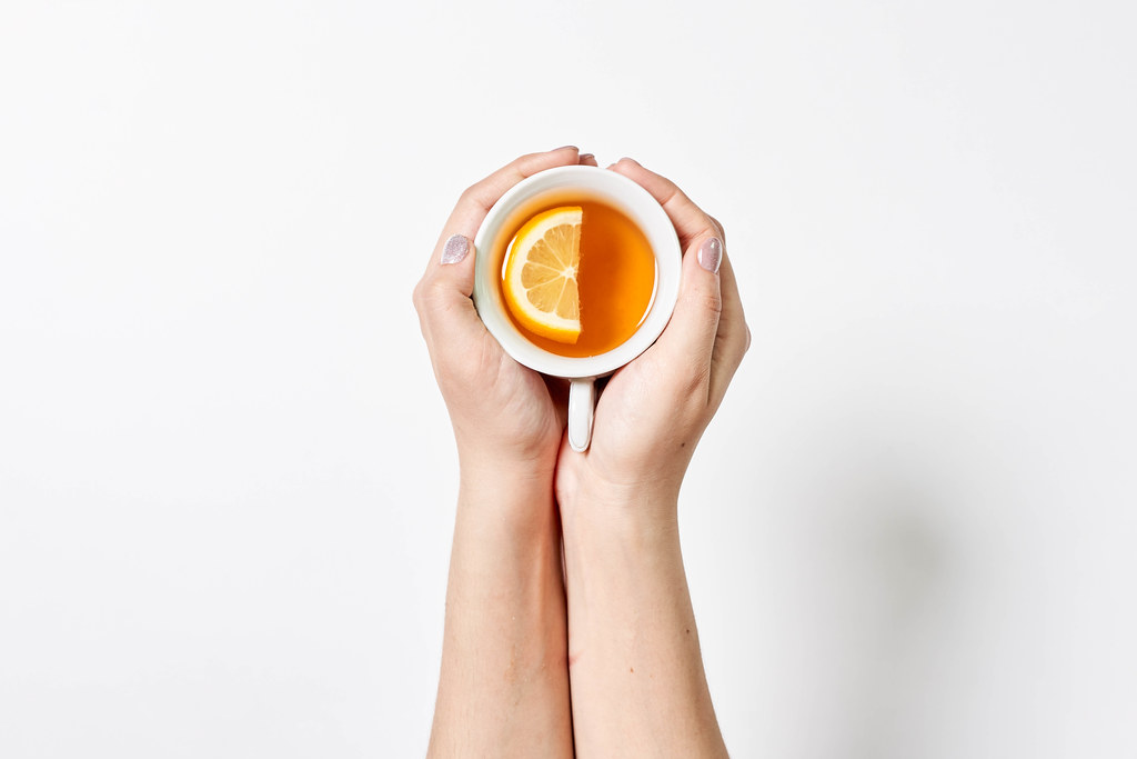 Female hands holding a cup of tea with lemon on white background
