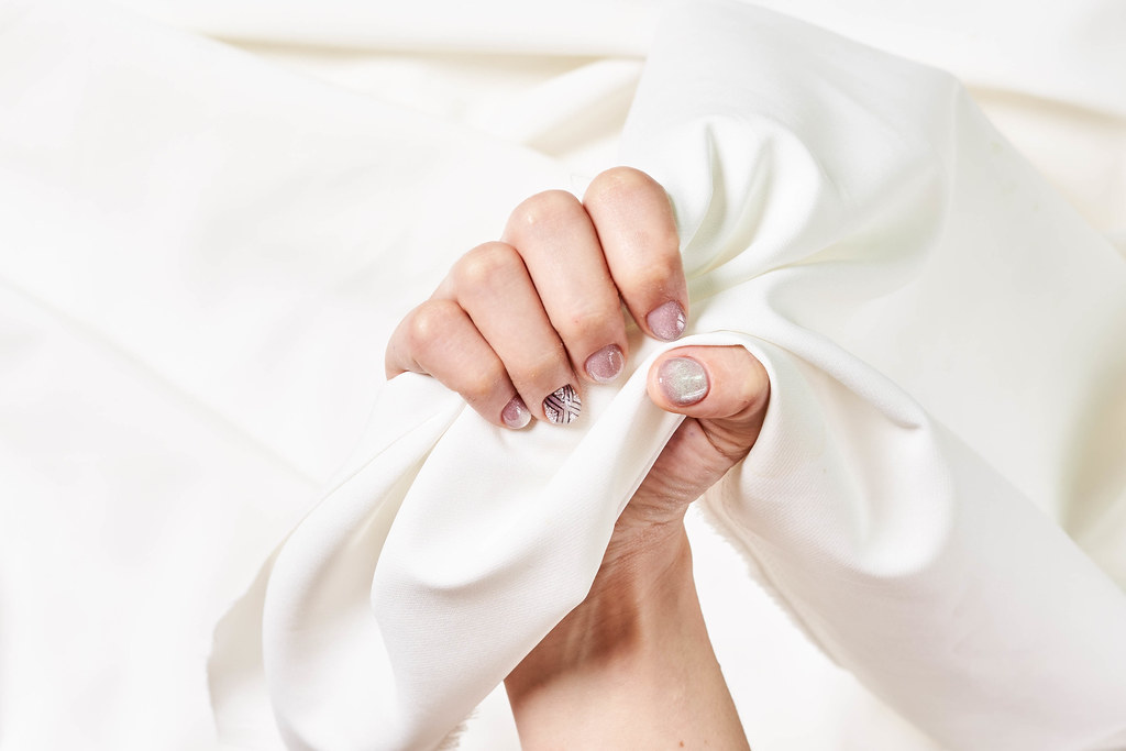 Female hands with beautifully manicured nails on silk fabric