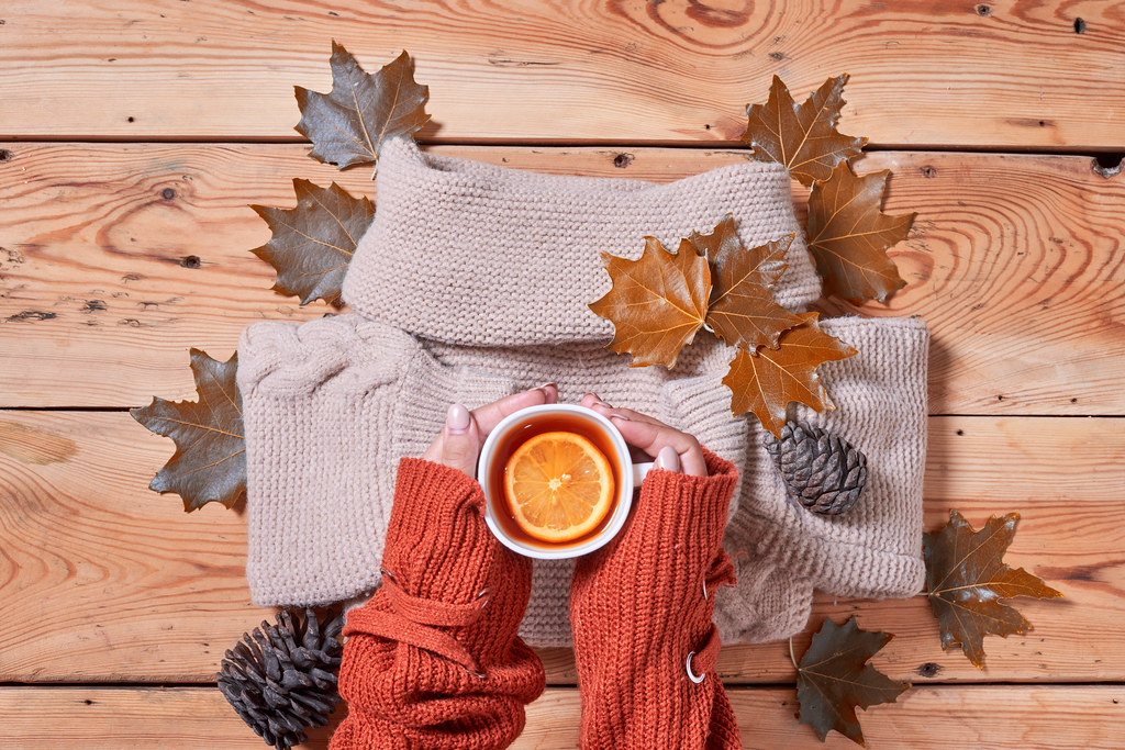 Female holds a cup of hot lemon tea over fall leaves