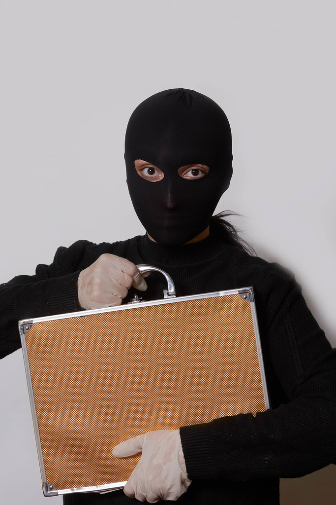 Female thief with balaclava on head holding a suitcase with cash and gems