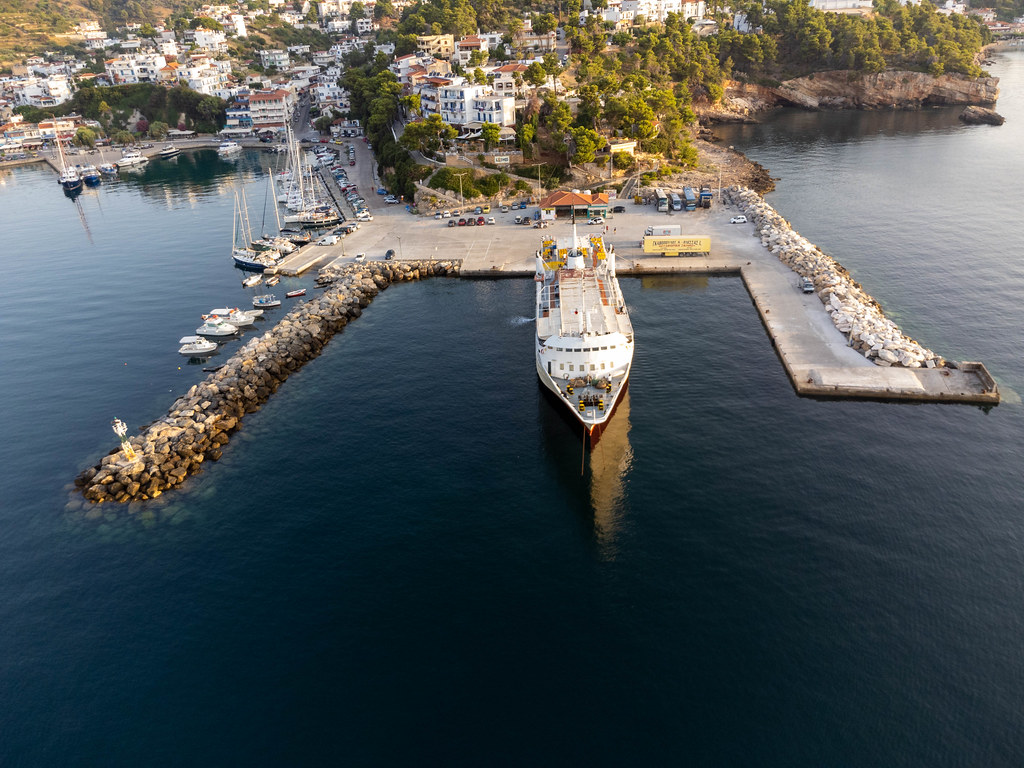 Ferry terminal, harbour and village of Patitiri on Alonnisos seen from the sea. Drone photo