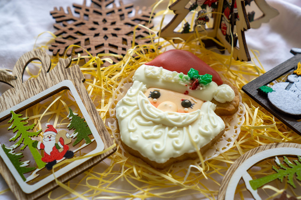 Festive Background Wooden Santa Claus Christmas Decoration next to a Gingerbread Cookie in Santa Claus Form with white and red Icing