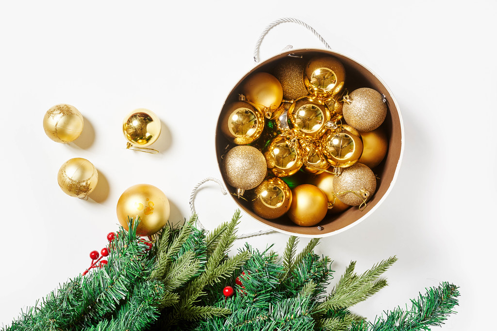 Festive golden colored Christmas decorations on white background