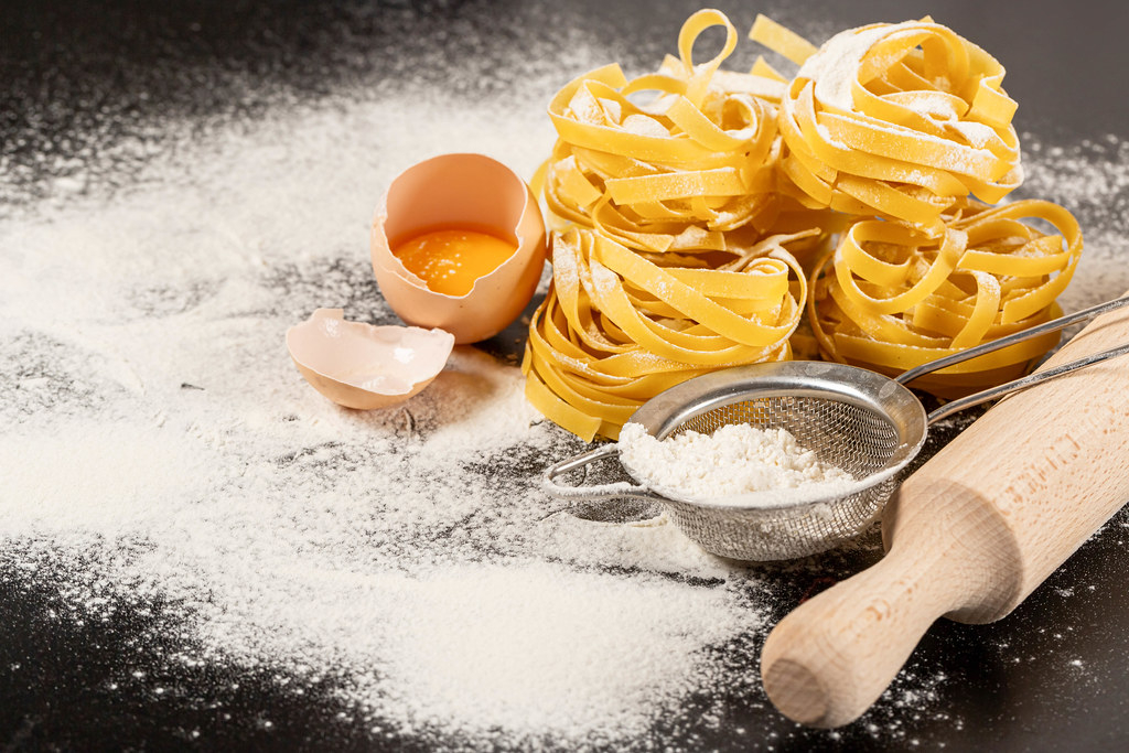 Fettuccine pasta ingredients for Italian food on dark background