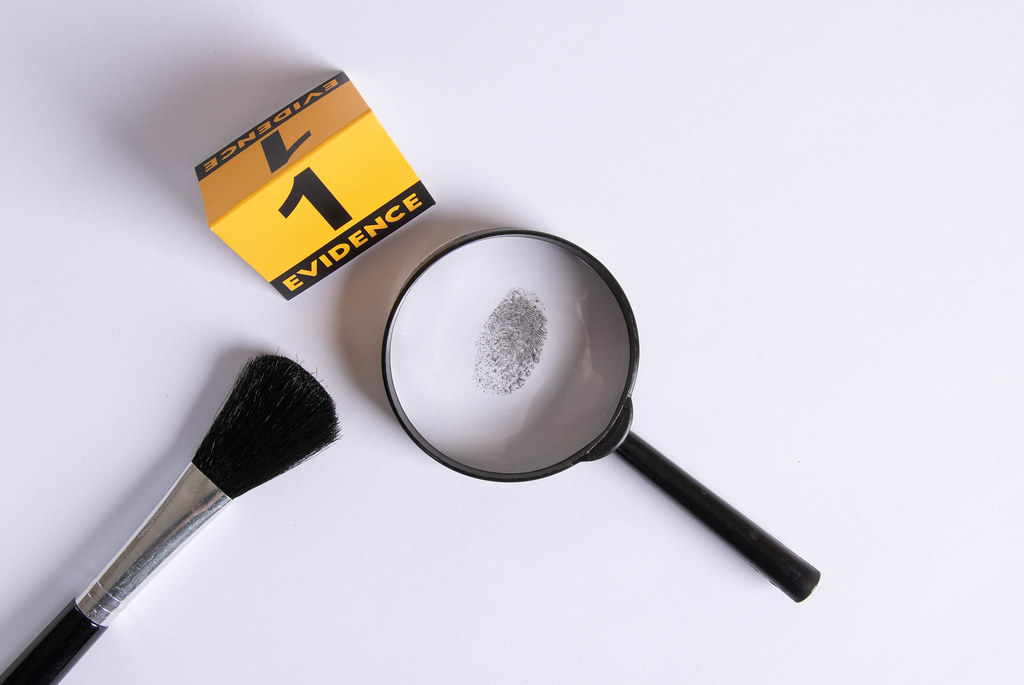 Fingerprint under a magnifier with evidence marker
