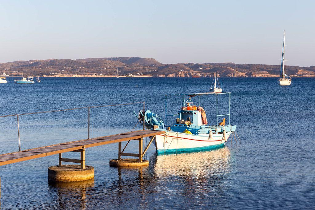 Fischerboot am Pier in Adamas auf der griechischen Insel Milos, bei ruhigem Meer