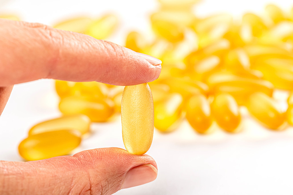 Fish oil capsule in hand, health care and medical concept