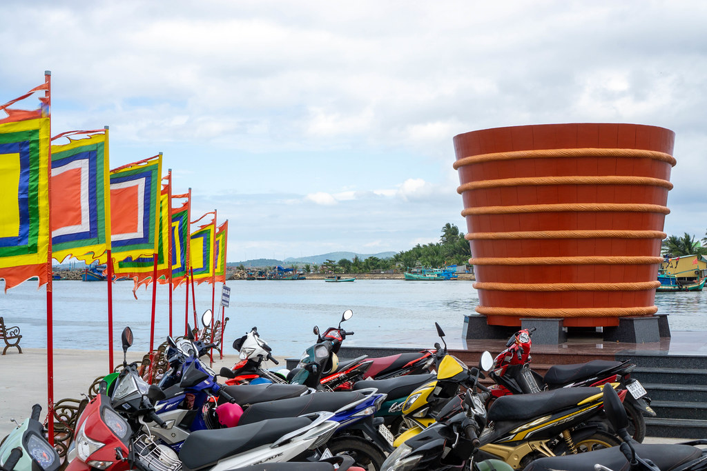 Fish Sauce Barrel Statue next to a Motorbike Parking and Buddhist Flags at Phu Quoc Harbour, Vietnam with Fishing Boats in the Background