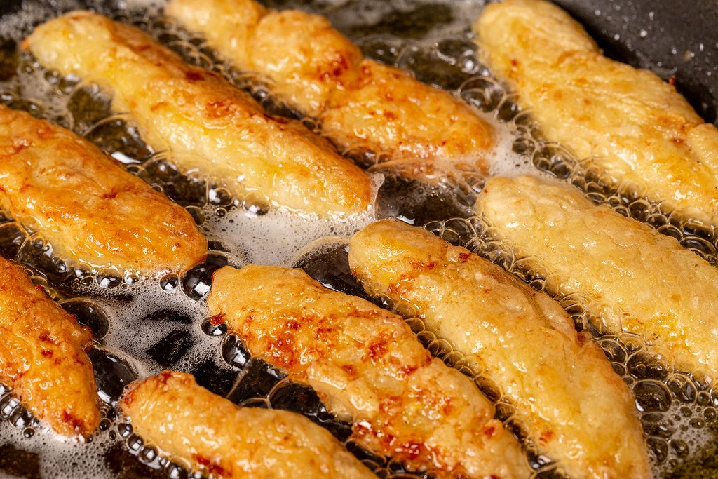 Fish sticks in batter in a frying pan with boiling oil, close-up