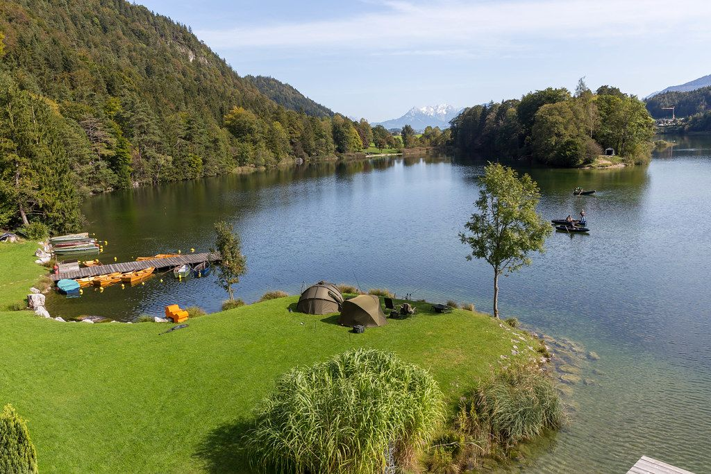 Fishing at Reintalersee in Tyrol: tents and camping chairs by the shore, anglers on wooden boats