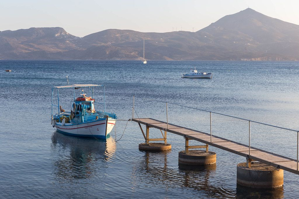 Fishing boat at the pier in Adamas on the Greek island of Milos, with a tranquil sea