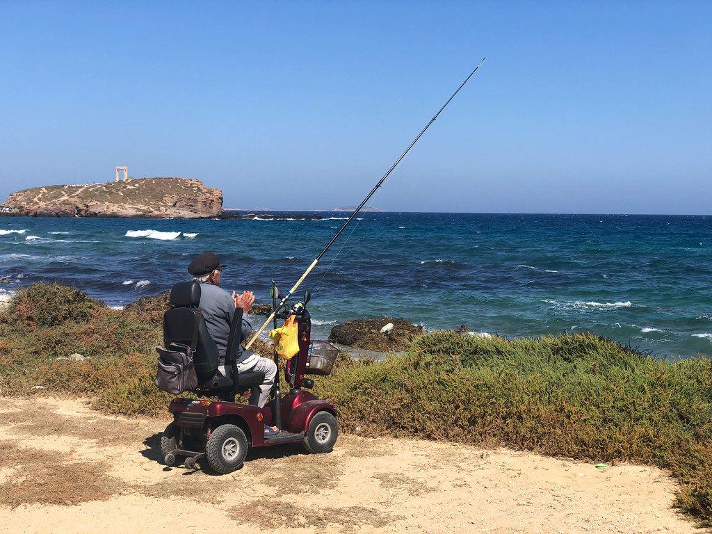 Fit im Alter: Senior angelt im Elektromobil am Strand von Naxos, Griechenland