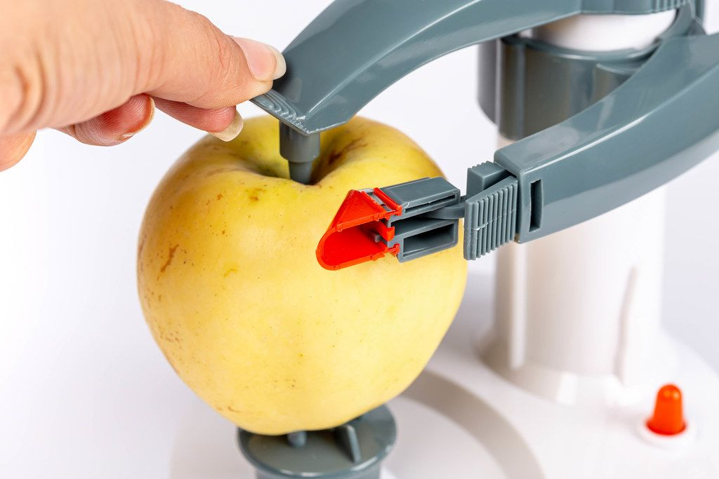 Fixing an apple in a peeling machine, close-up