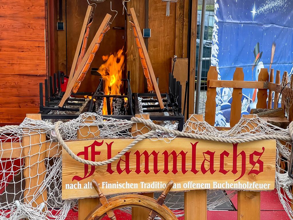 Flammlachs nach alter finnischen Tradition an offenem Buchenholzfeuer am Neumarkt in Köln