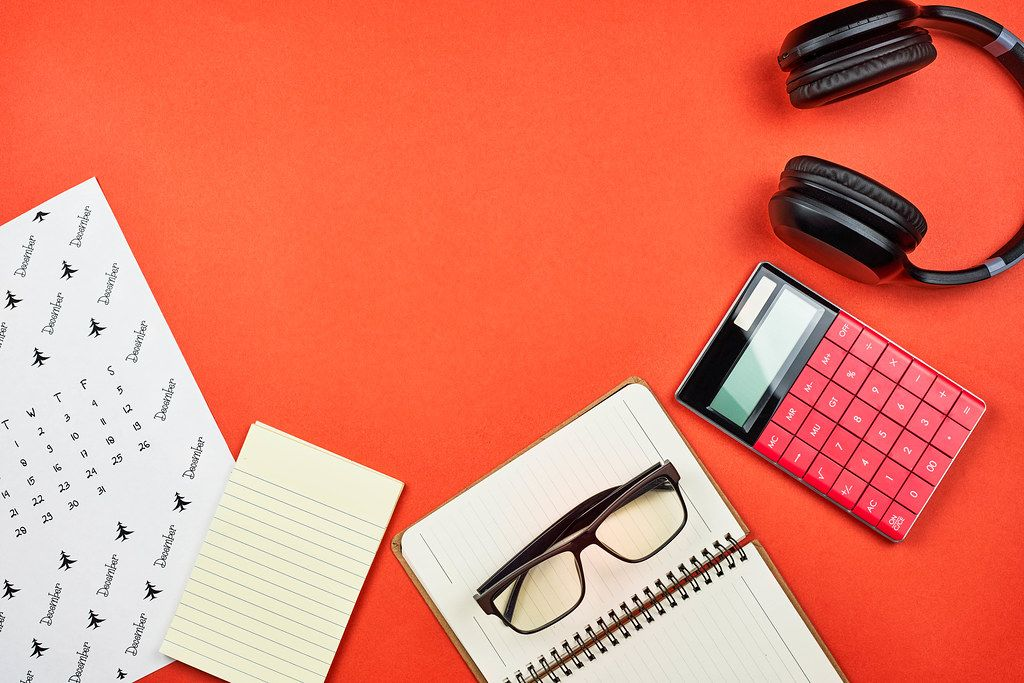 Flat lay arrangement of office supplies on a bright red background