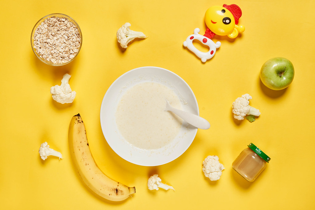 Flat lay composition with bowl of healthy baby food on yellow background