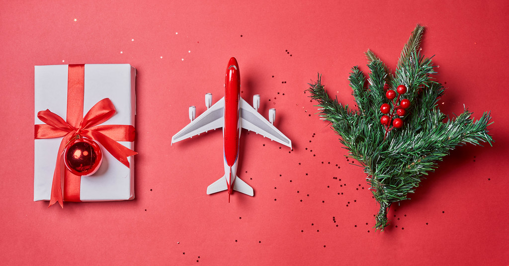 Flat lay composition with toy airplane, gift box and christmas tree on red background
