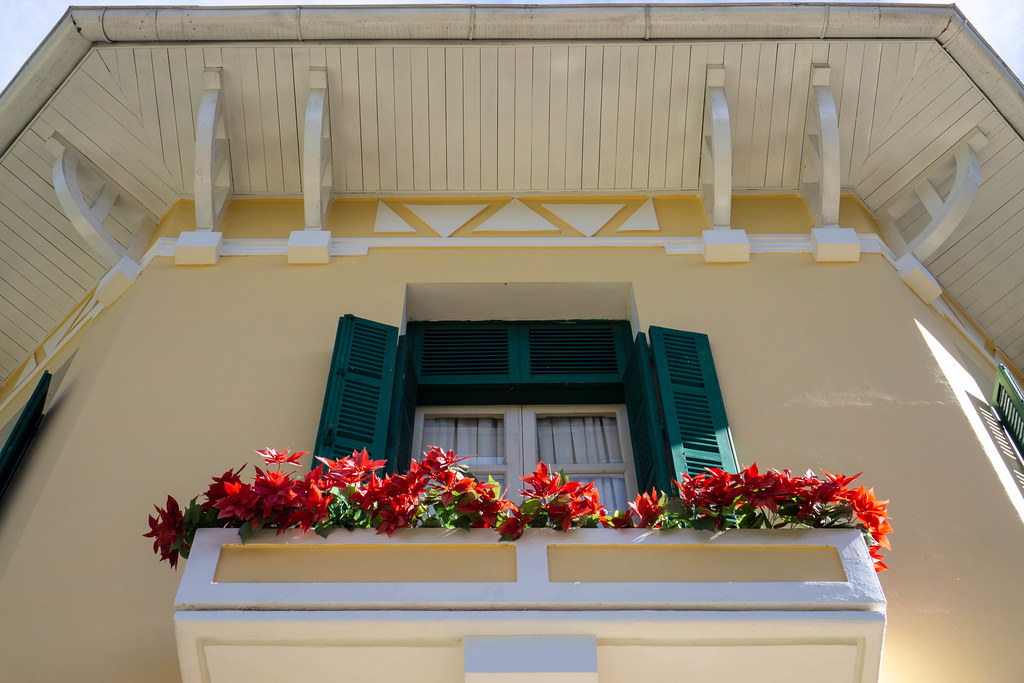 Flowers in front of a Wooden Window with Wooden Sun Blinds at the Bao Dai King Palace with French Architecture in Da Lat, Vietnam