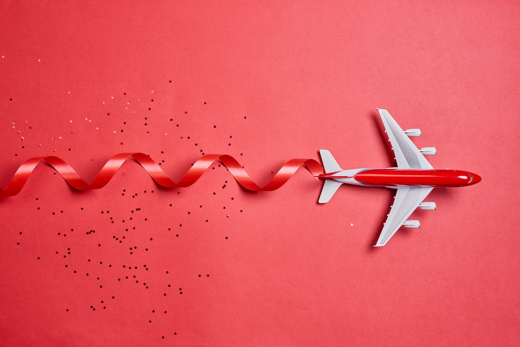 Flying to vacation for Christmas holidays. Airplane on red with festive ribbon