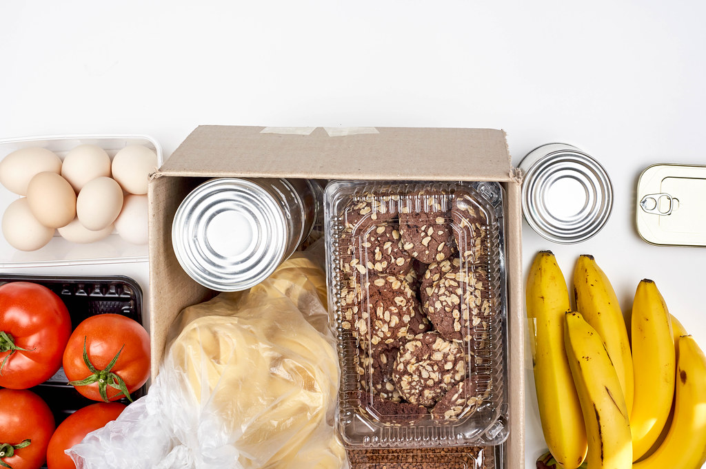 Food bank donation with cookies, tagliatelle noodles, tomatoes, bananas, eggs and tin cans in a box