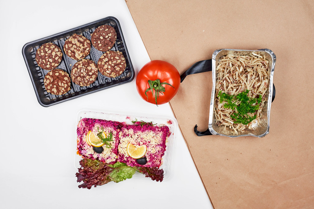 Food bank donations: cookies, a tomato, lettuce, noodles and beetroot dish in one-way packaging