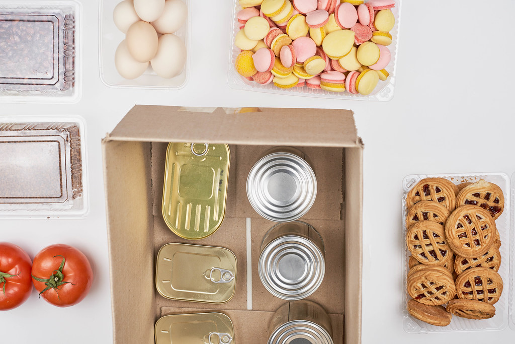 Food bank: top view of tin cans in a cardboard box surrounded by tomatoes, eggs, cookies, dried fruit