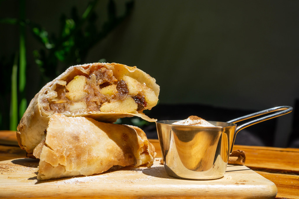 Food Photo of Apple Strudel Desssert with Raisin and Fresh Apples on a Wooden Board with Whipped Cream and Cinnamon in a Restaurant