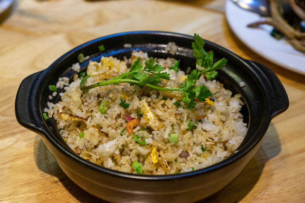 Food Photo of Fried Rice in a Ceramic Cooking Pot with Fried Eggs, Salted Fish, Parsley and Vegetables in a Restaurant
