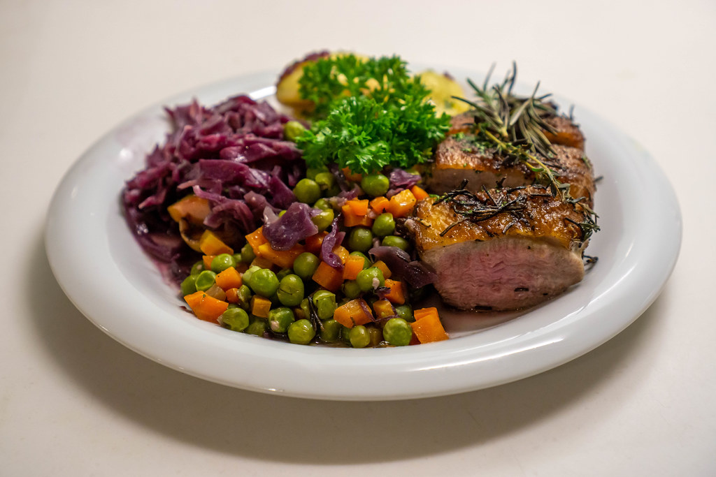 Food Photo of Pan Seared Duck Breast with Carrots, Peas, Red Cabbage with Apples, Potato Dumplings and Parsley on a White Ceramic Plate