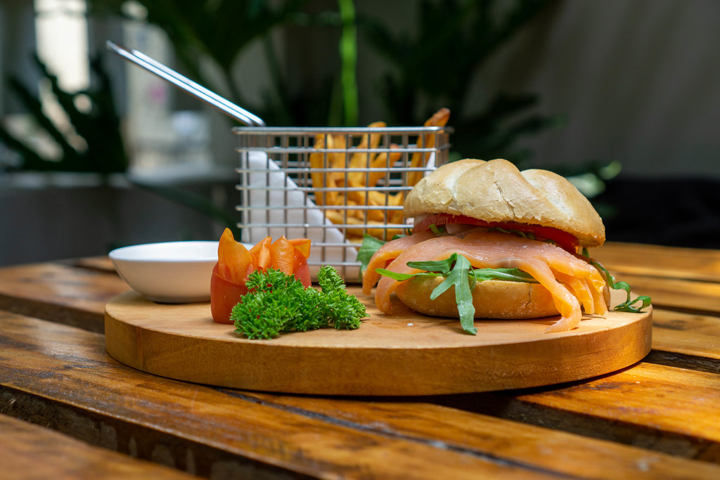 Food Photo of Smoked Salmon Sandwich with Arugula, Tomato and Honey Mustard Sauce in a German Bread Roll on a Wooden Board with Parsley, Tomatoes and a Basket with French Fries in a Restaurant