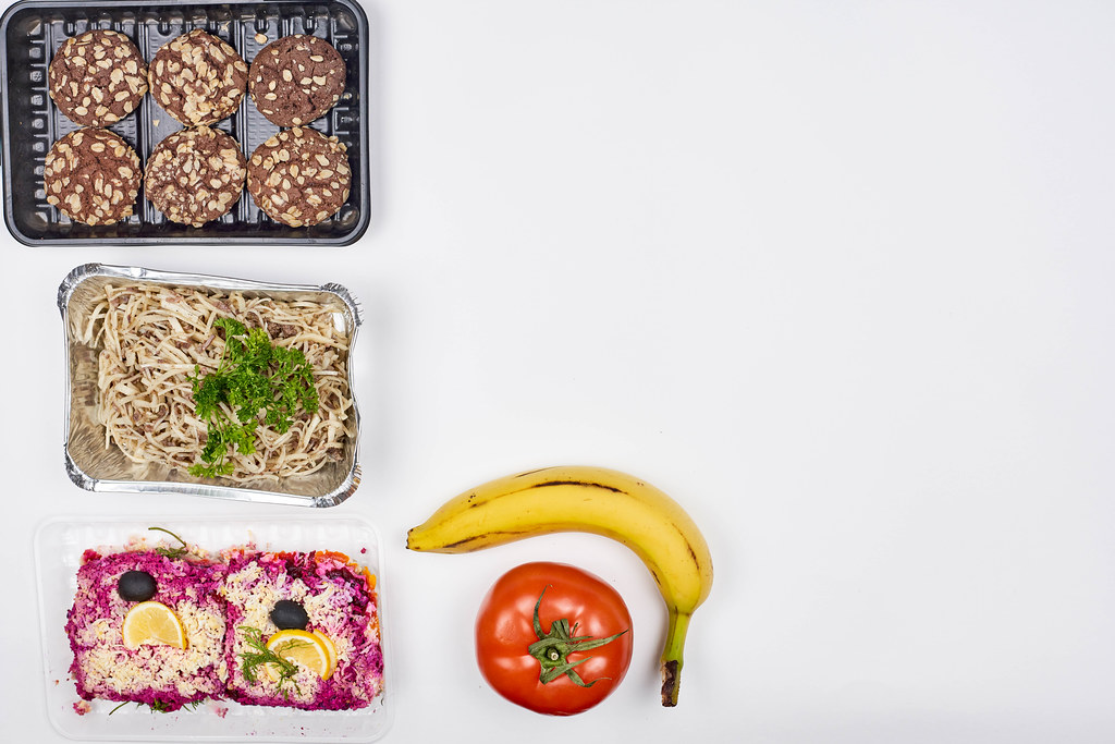 Food to go served in one-way packaging at food bank. White background with copy space to the right