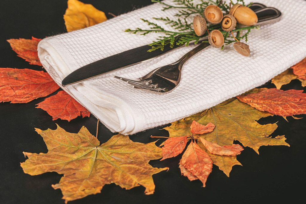 Fork and knife with autumn leaves and acorns