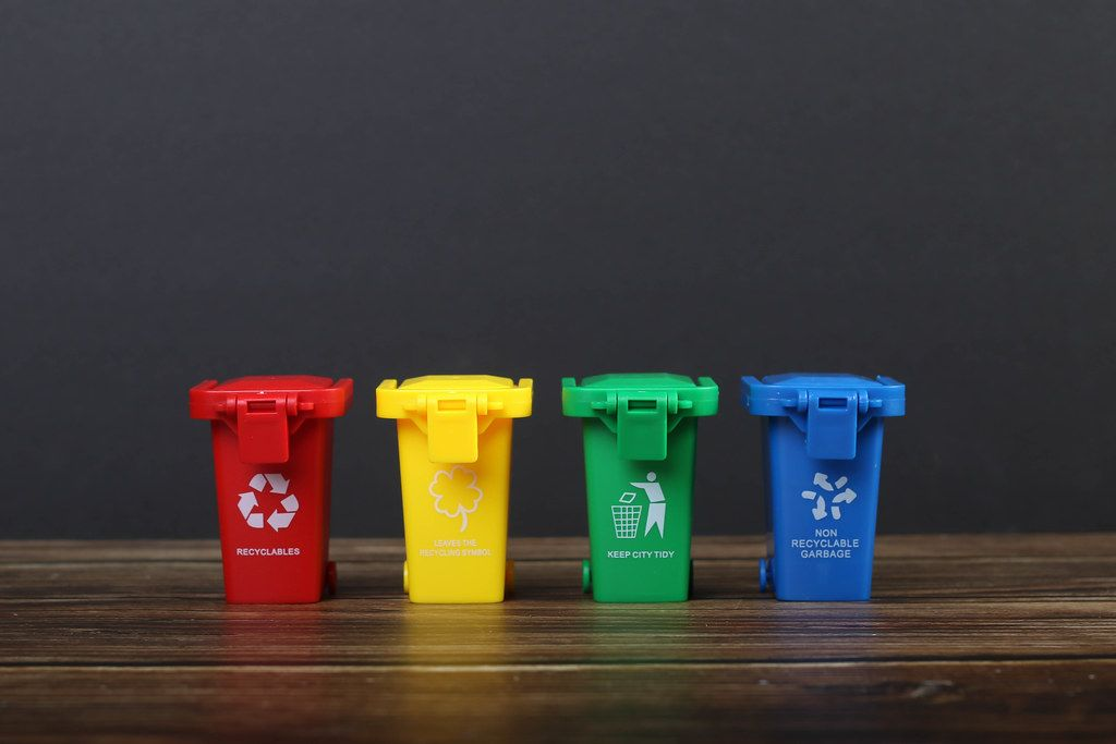 Four colorful recycle bins on wooden table