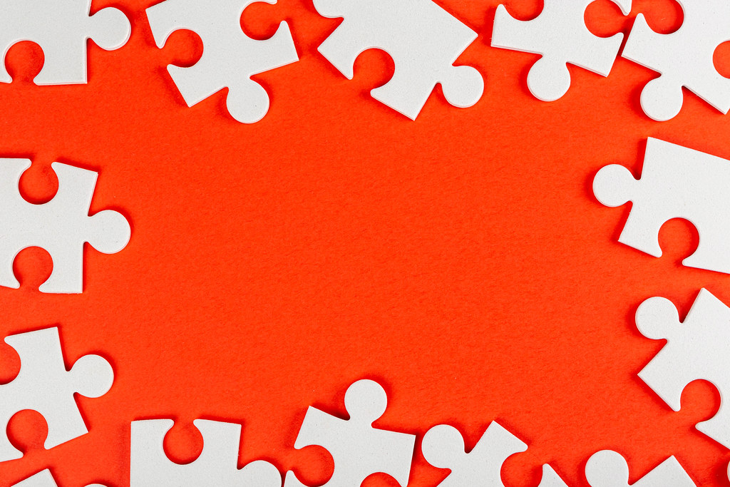 Frame made of white puzzle pieces on a red background