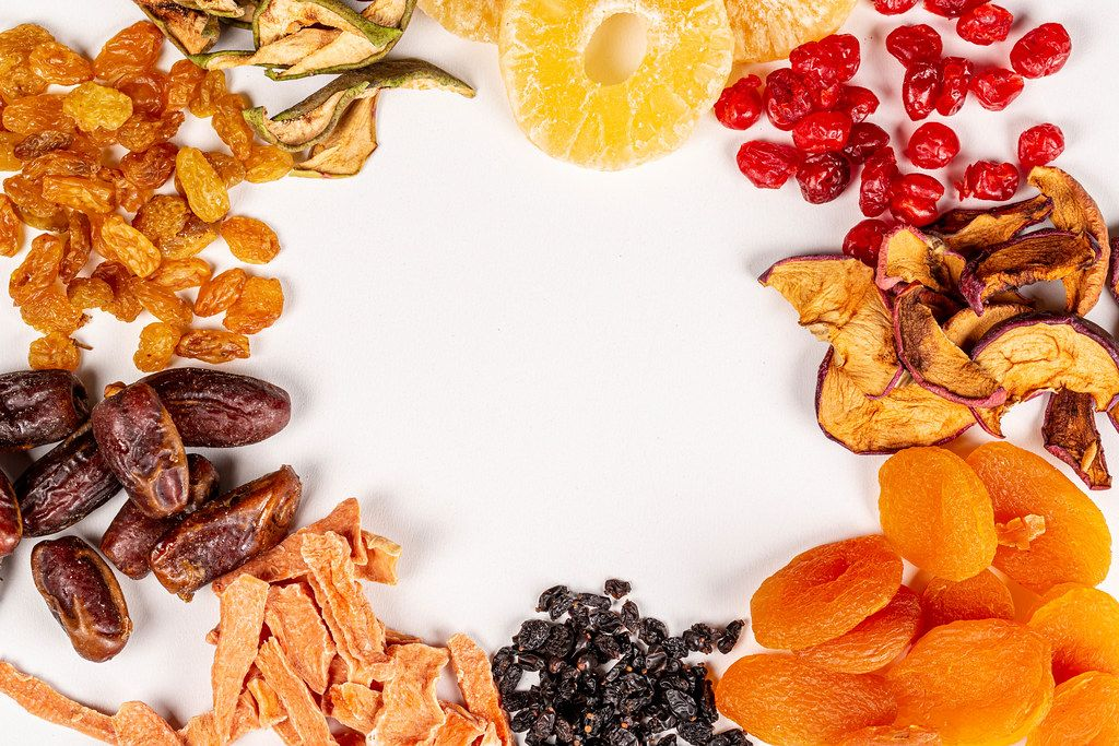 Frame of different dried fruits on white with free space