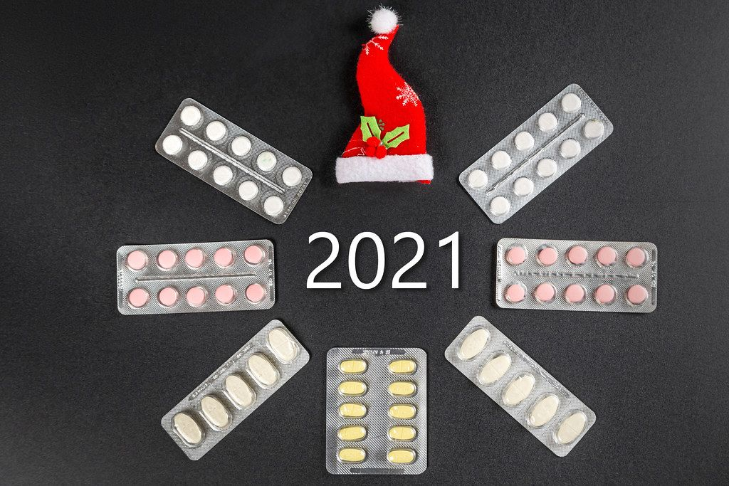 Frame of pills in blisters and santa hat on a black background with the inscription 2021 in the center