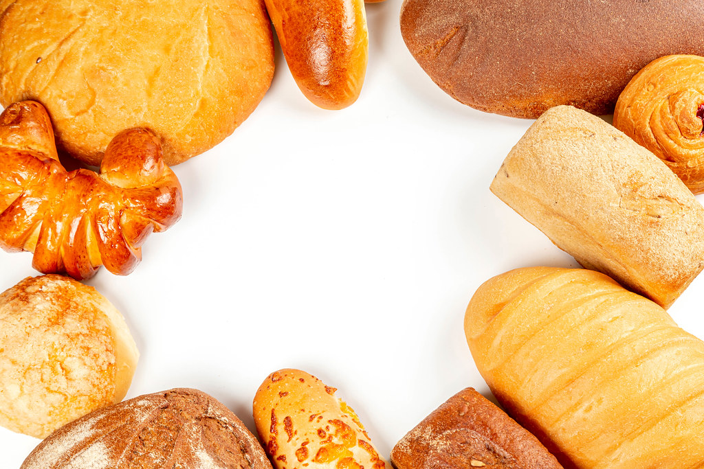 Frame with different types of bread, buns and pies on a white background, top view with free space