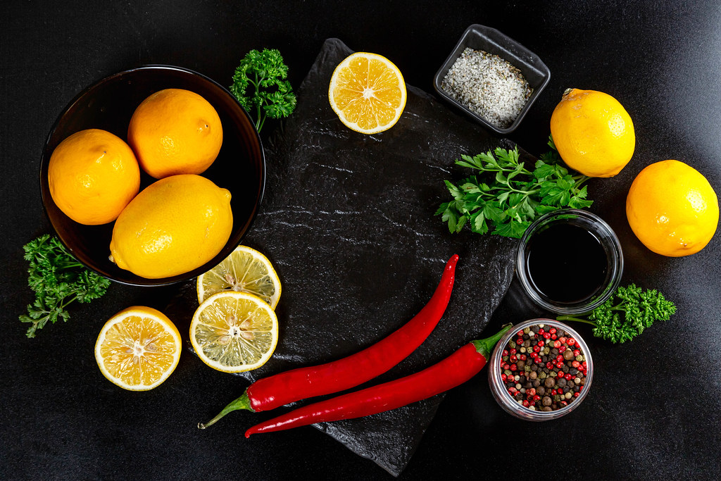 Frame with spices, lemon and herbs on a dark background, top view