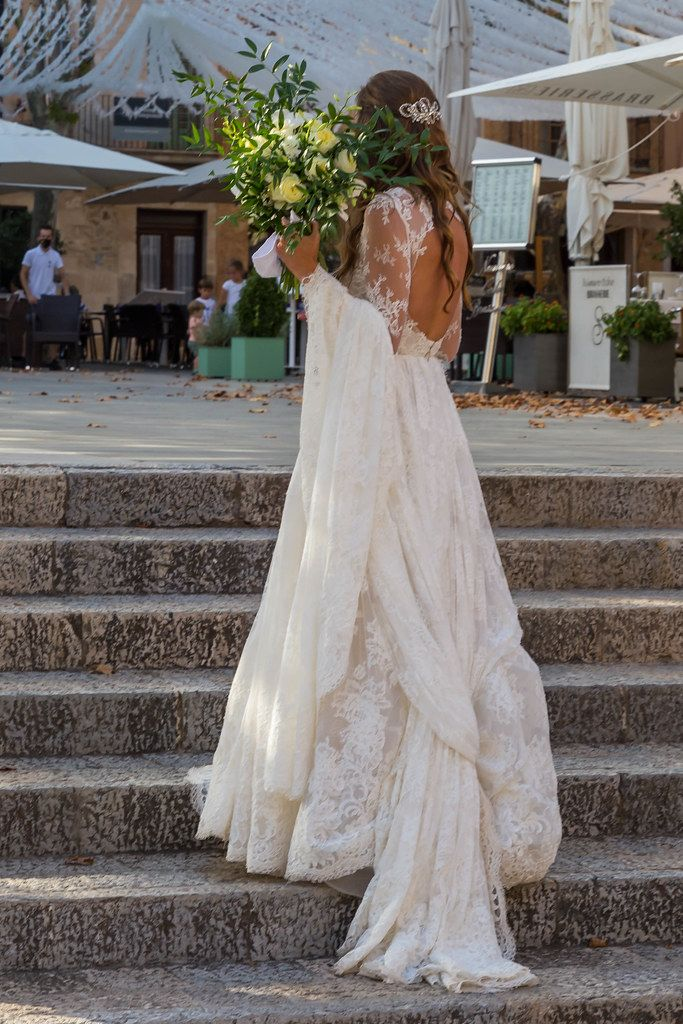 Frau in weißem rückenfreiem Brautkleid mit Blumenstrauß steht auf einer Treppe auf Mallorca