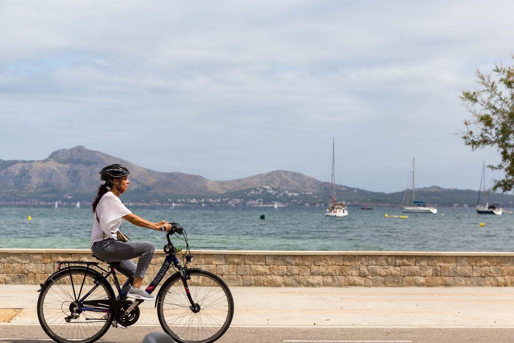 Frau mit weißer Bluse und schwarzem Fahrradhelm fährt Fahrrad am Meer entlang auf Mallorca