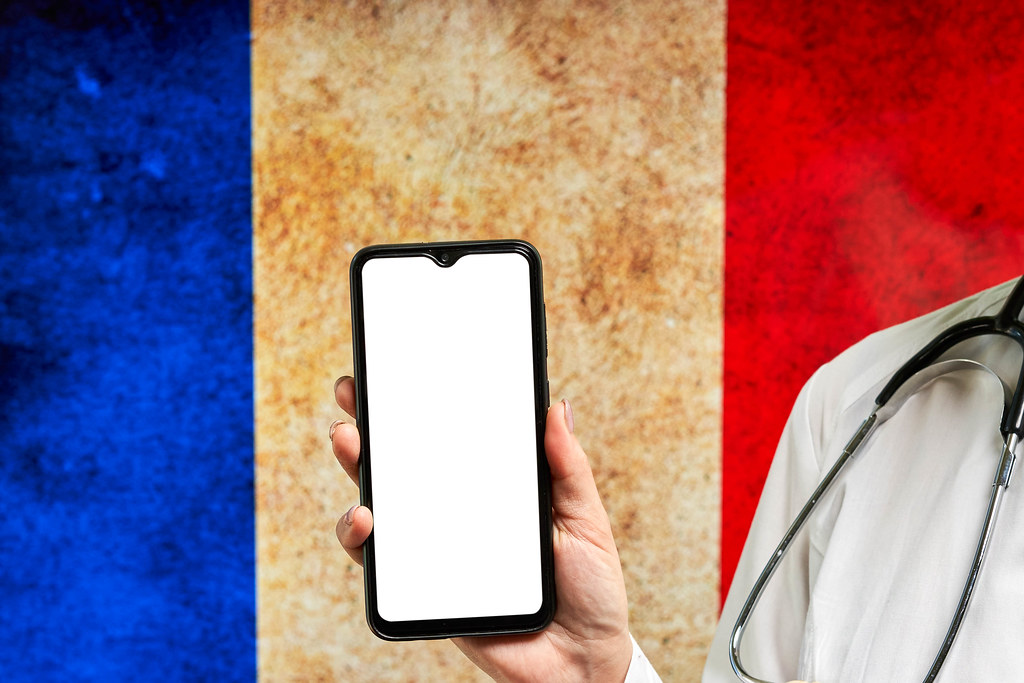 French doctor holding a smartphone with empty screen