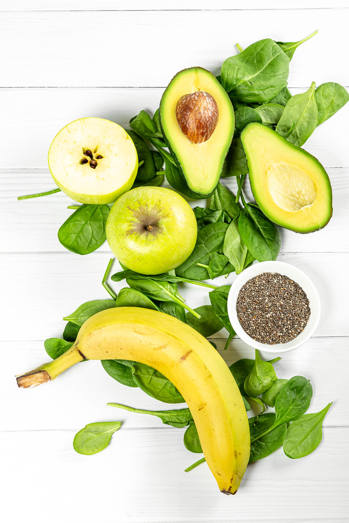 Fresh avocado, apples, spinach leaves and chia seeds on a white wooden background, top view