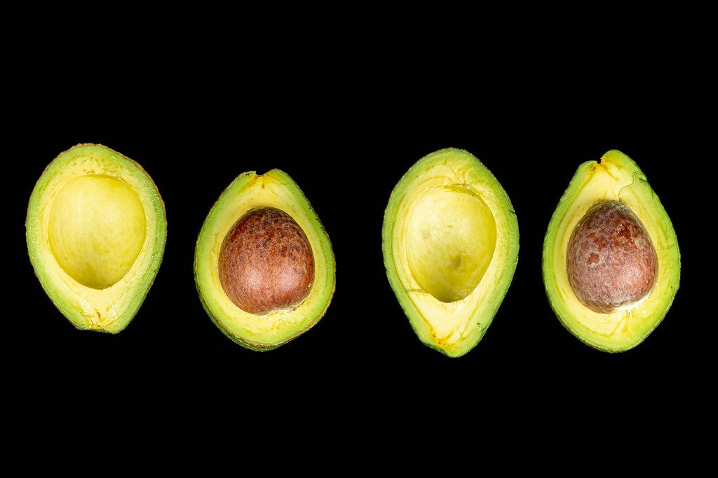 Fresh avocado halves with and without seeds on black background, top view