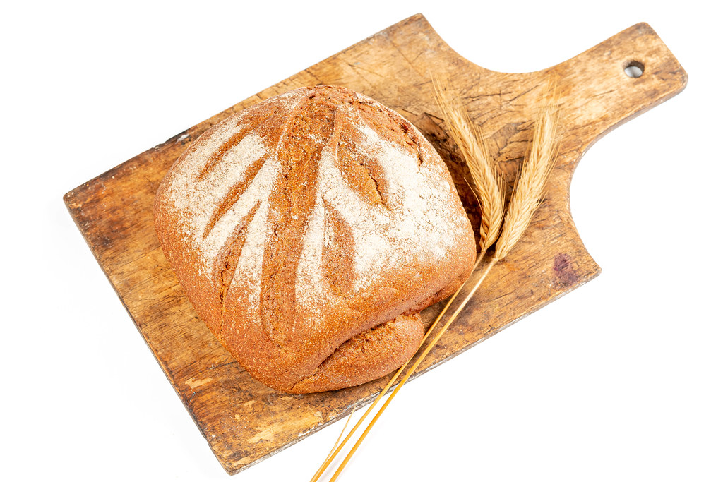 Fresh baked rye bread on wooden kitchen board with spikelets