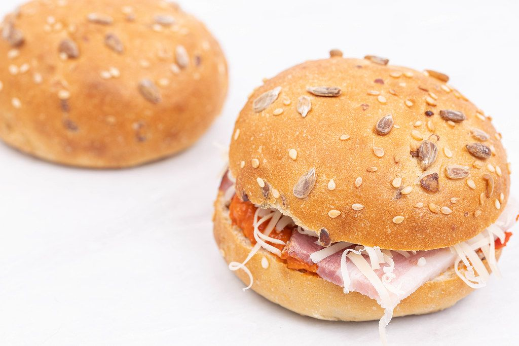 Fresh Buns with Ham Paprika spread and grated Cheese above white background