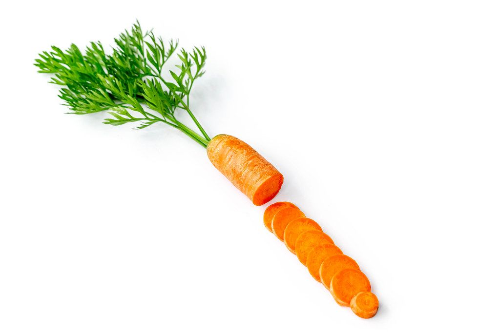 Fresh carrot slices with green leaves on white background