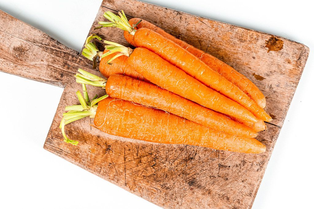 Fresh carrots on a kitchen board, top view